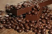 Coffee beans with chocolate glaze and dark chocolate on wooden background