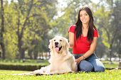 stock photo of dog park  - Girl sitting in park with her pet dog - JPG