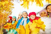 Many smiling kids with rake and yellow leaves