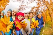 Smiling small children in park with yellow leaves