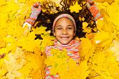Little African girl covered with maple leaves