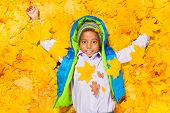 African boy laying in autumn maple leaves