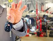 Hand with a car key. Auto repair service