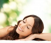 beauty, people and health concept - beautiful young woman lying with closed eyes over green background