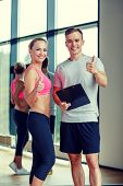 fitness, sport, exercising and diet concept - smiling young woman with personal trainer in gym showing thumbs up