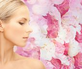 beauty, people and health concept - beautiful young woman face over pink floral background