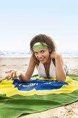 Young attractive mixed race girl with Brazil flag on beach