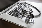 Medical Stethoscope Resting on Laptop Computer Keyboard.