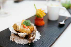 stock photo of oyster shell  - Tempura fried oyster in shell on plate - JPG