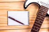 picture of sounding-rod  - electric guitar and memo pad on wooden table - JPG