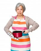 stock photo of saucepan  - Asian housewife hold saucepan with oven glove  - JPG