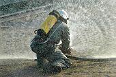 picture of water jet  - Firefighter in protective suit works with water cannon - JPG