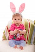 image of baby easter  - Cheerful baby girl with bunny ears holding lilla Easter egg and sitting on fluffy blanket - JPG