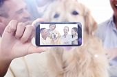 image of dog clothes  - Hand holding smartphone showing against portrait of smiling family sitting together with their dog - JPG