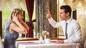 stock photo of conflict couple  - Image of young couple arguing at restaurant  - JPG