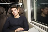 pic of passenger train  - Young man sleeping while traveling on a train sitting in a passenger coach with his head resting on his hand and eyes closed - JPG