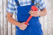 pic of pliers  - Repairman holding adjustable pliers against digitally generated grey wooden planks - JPG