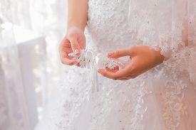 foto of garter-belt  - Bride holds a garter in her hands. ** Note: Shallow depth of field - JPG