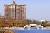 Residential skyscraper and public park in Jilin. North China city in autumn season. Oriental bridge.