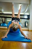 Fit woman performing pilate on exercise ball in fitness studio poster
