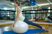 Fit woman exercising on fitness ball in fitness studio poster
