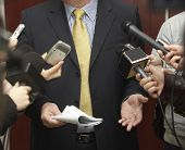 image of public speaking  - close up of conference meeting microphones and businessman - JPG