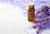 Lavender essential oil,   sprigs of lavender and  mineral bath salts on  the wooden table.  Selectiv poster