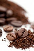 Pile of roasted and ground brown coffee beans isolated on white background