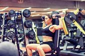 sport, fitness, bodybuilding, weightlifting and people concept - young woman with dumbbell flexing m poster
