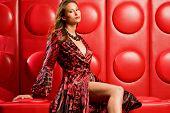 Beautiful fashion model sits on funky modern red lounge