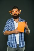 Hipster Bearded Man Wear Funny Eyeglasses Hold Notepad Or Book. Bright Up Your Day. Read This Book.  poster