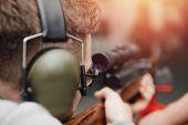 Man Directs Firearm Gun Pistol At Target Firing Range Or Shooting Range. poster