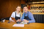 Happy Man And Woman Going Through Paperwork Together In Their Restaurant. Small Family Restaurant Ow poster
