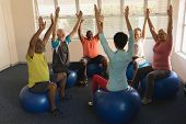 Front view of female trainer training senior people in performing exercise ball at home poster