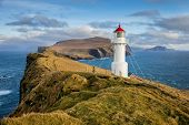 View of the Holmur Lighthouse on the island of Mykines in the Faroe Islands. poster