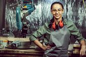Smiling Craftswoman Grinding Timbers With Special Machine. Beautiful Woman Wearing Safety Glasses. C poster
