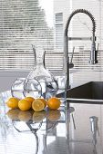 carafes of water and lemons in modern kitchen - freshness