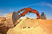 stock photo of grub  - Excavator during earth moving works outdoors at sand quarry - JPG