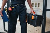 Cut View Of Handyman Holding Tool Box And Plastic Tablet In Hands. He Stand In Kitchen. Guy Wear Spe poster