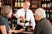 Wine bar senior couple enjoy drink professional barman pour glass