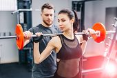 Fitness Girl Having Weight Training With Assistance Of Coach In Gym. Personal Fitness Instructor. Pe poster