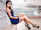 beautiful young brunette woman wearing a blue mini dress in the street