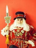 Frown Senior Man Beefeater Yeomen Warder Or Male Royal Guard Bodyguard In Uniform With Spear On Red  poster