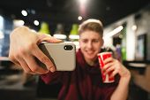 Young Man With A Drink In His Hands Makes A Selfie In A Fast Food Cafe, A Smartphone Close-up And In poster