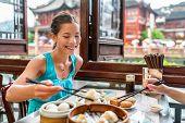 Chinese woman eating at Shanghai restaurant Xiao long bao / xiaolongbao soup dumplings typical food  poster