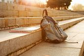 stock photo of derelict  - Old denim school backpack with copybooks left on the stone steps - JPG