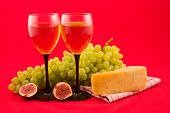 Wine, Cheese And Fruits On A Red Background