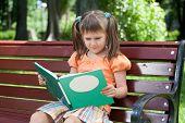 Little Cute Girl Preschooler With Book On Bench In Park