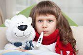 Niña enferma con termómetro abraza oso de juguete en la cama