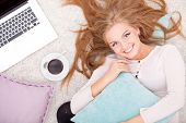 Overhead view of young woman lying on back on carpet alongside laptop, coffee, daydreaming